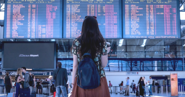 A woman in a brown skirt, t-shirt and black backpack standing in the airport in front of the departure boards, shown from behind.