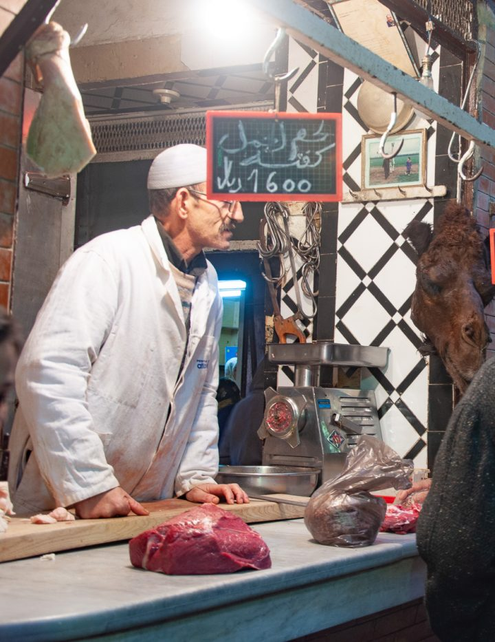 A butcher stall in the Fes medina with meat on the counter and a butcher dressed in white behind the counter