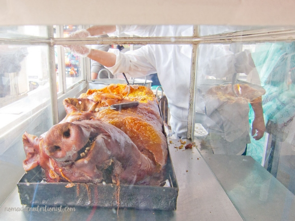 Front view of Lechona Tolimense shows the pig head with body stuffed with ingredients in the background.