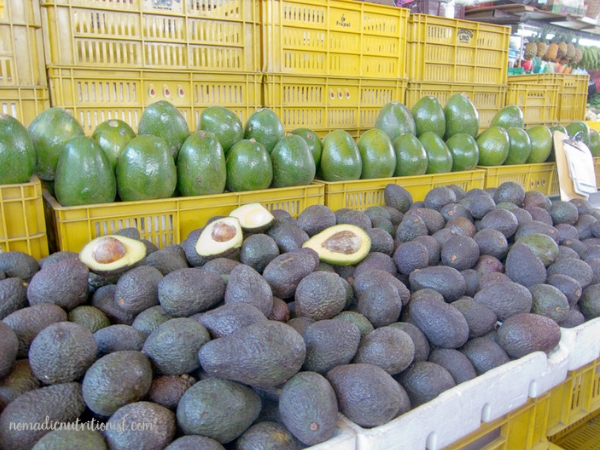 A vendor's table with alligator avocados in front and Florida avocados above at Plaza de Paloquemao in Bogota, Colombia.