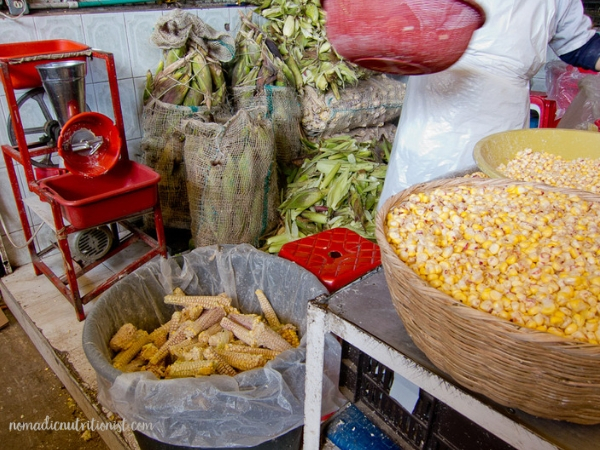 A corn vendor's booth with a large bowl of corn kernels, a garbage pail with empty corn cobs, bags of ears of corn in the background at the Plaza de Paloquemao in Bogota, Colombia.