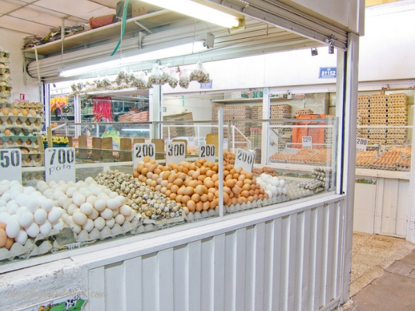 A vendor's booth piles of white and brown shelled eggs at the Plaza de Paloquemao in Bogota, Colombia.