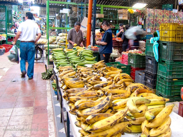 A vendor's table full of yellow and green plantains at the Plaza de Paloquemao in Bogota, Colombia. Shoppers appear in the aisles.