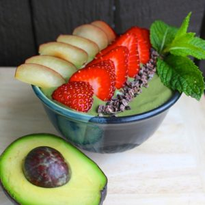 A green smoothie in a bowl, topped with slice strawberries, plums and a sprig of mint. A cut avocado sits in front of the bowl.