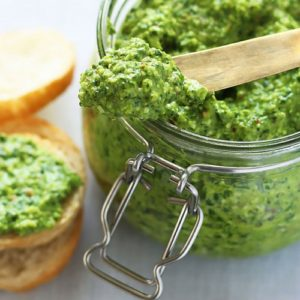 A top down shot of a jar of green pesto on a wooden spoon.