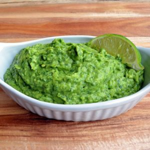 A white dish with green Spinach Guacamole on a wooden table.