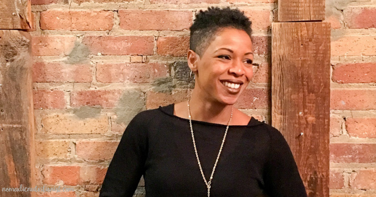 A headshot of a smiling black woman with short hair, a black shirt and gold hoop earrings.She is looking off to the right.