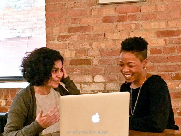 Two women, both with brown skin and short dark hair, sitting in front of a laptop. One woman is gesturing and one is laughing