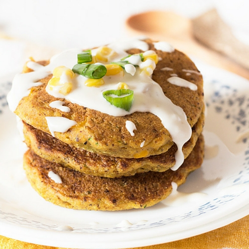 3 zucchini corn pancakes with sour cream on top