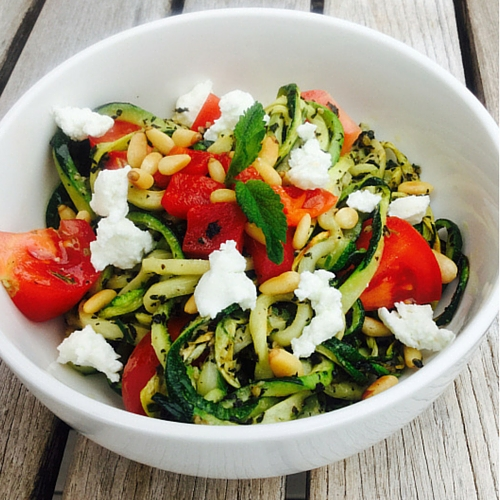 A white bowl with zucchini noodles, tomatoes and pesto