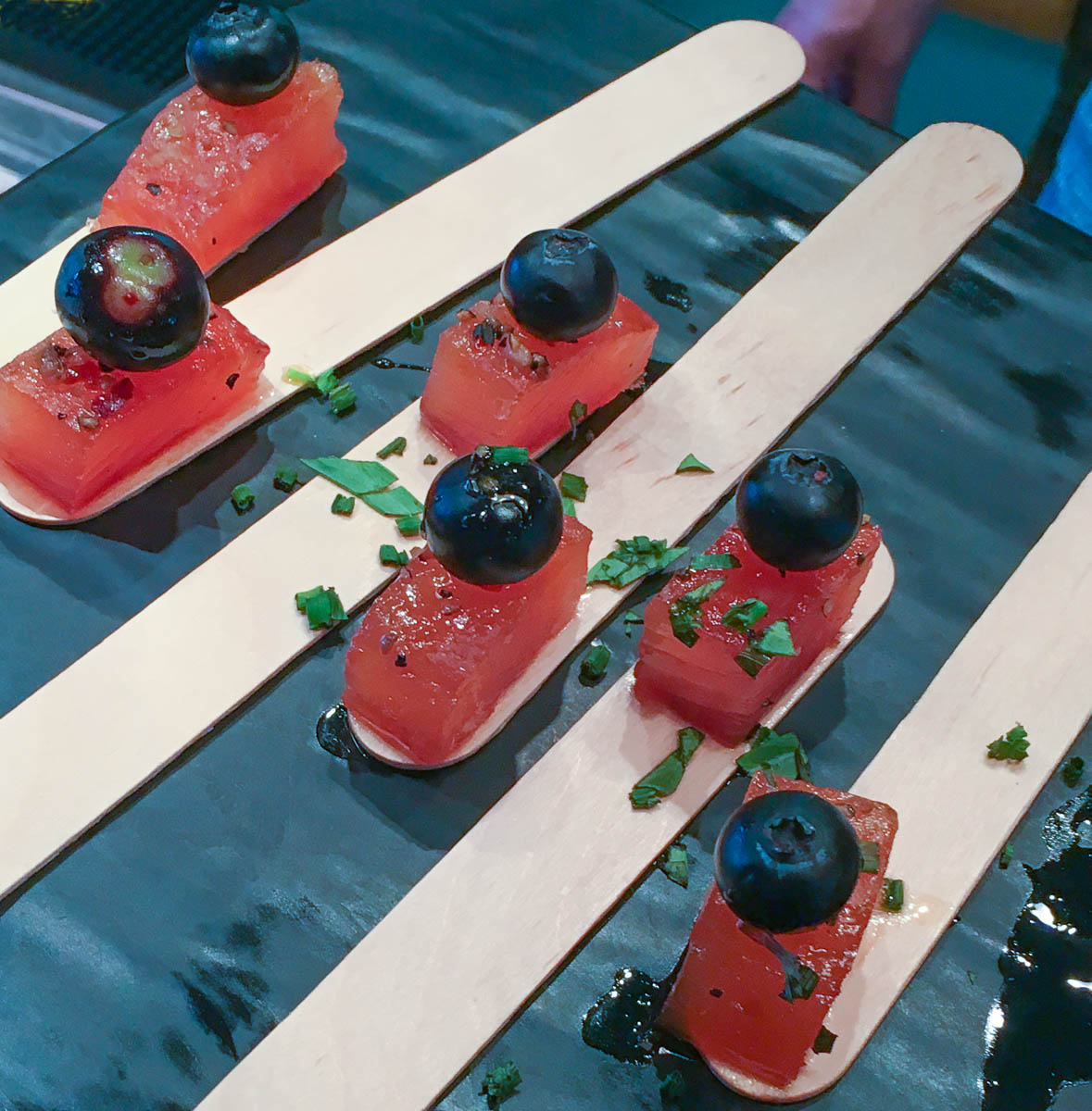 Several small cubes of salmon tartare topped with a fresh blueberry on a stick.