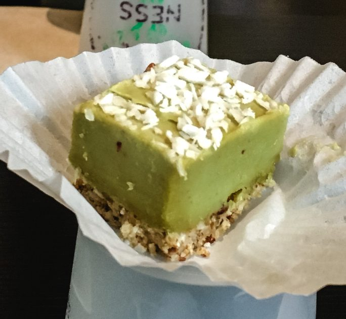 A square of raw key lime pie on a white paper holder.