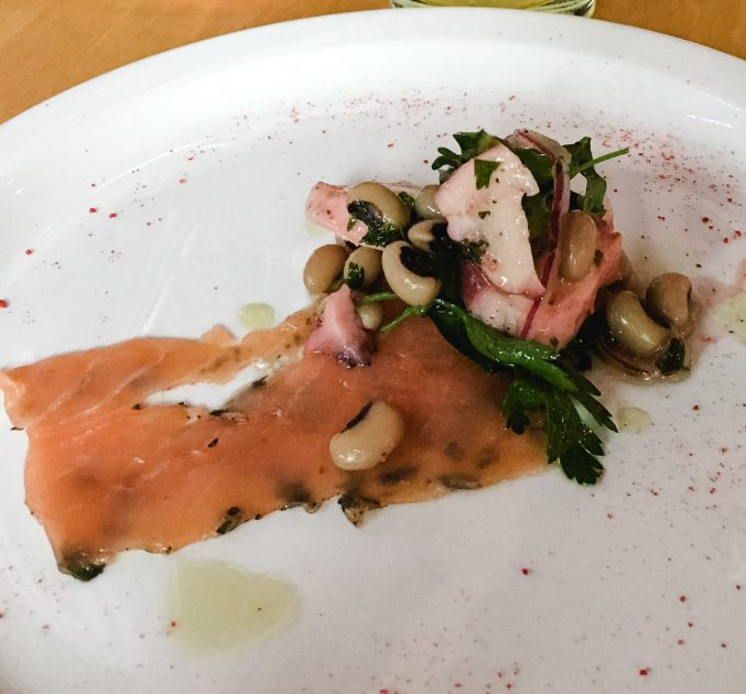 Thin slice of smoked salmon, black eyed peas and octopus ceviche arranged on a white plate.