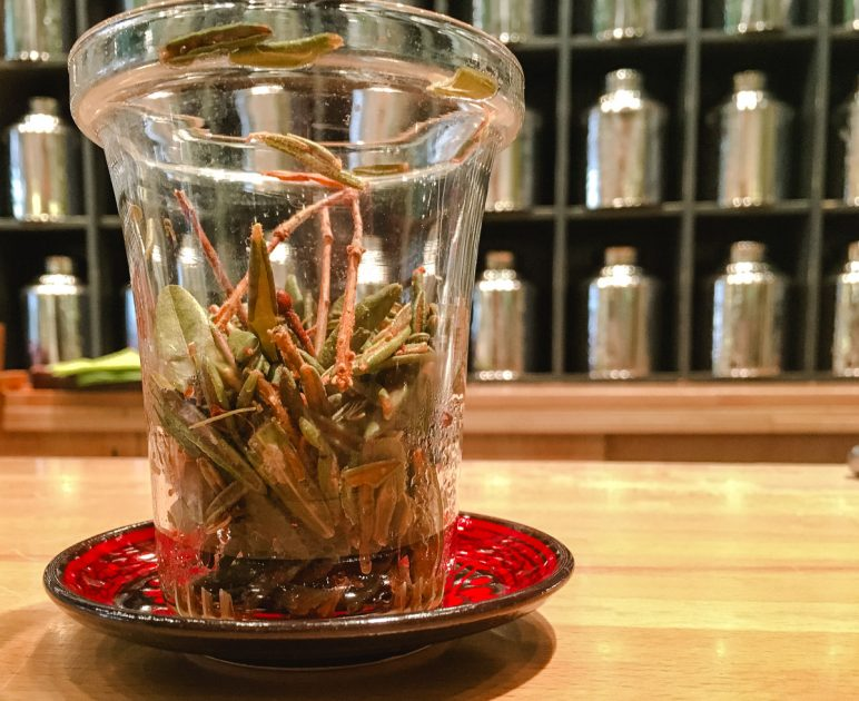 Close up of herbal tea leaves in a glass on a red saucer, with metal tea canisters in the background.
