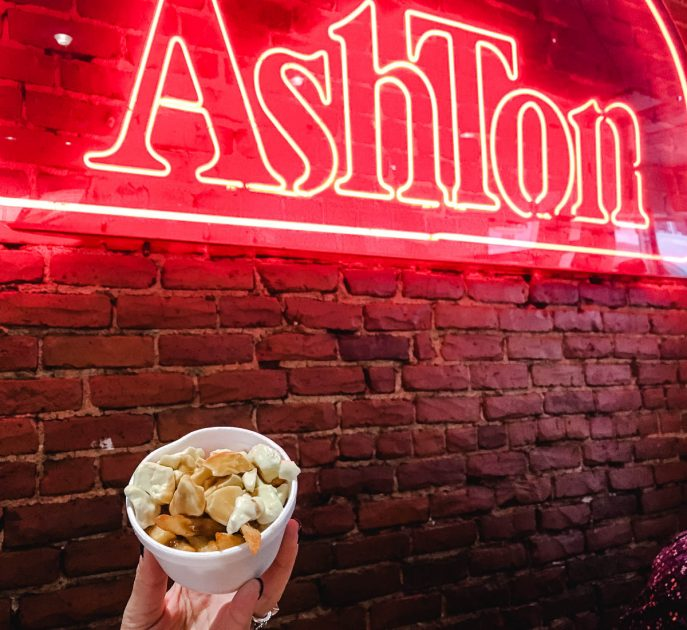 A hand holding a small portion of poutine under the neon Chez Ashton sign.