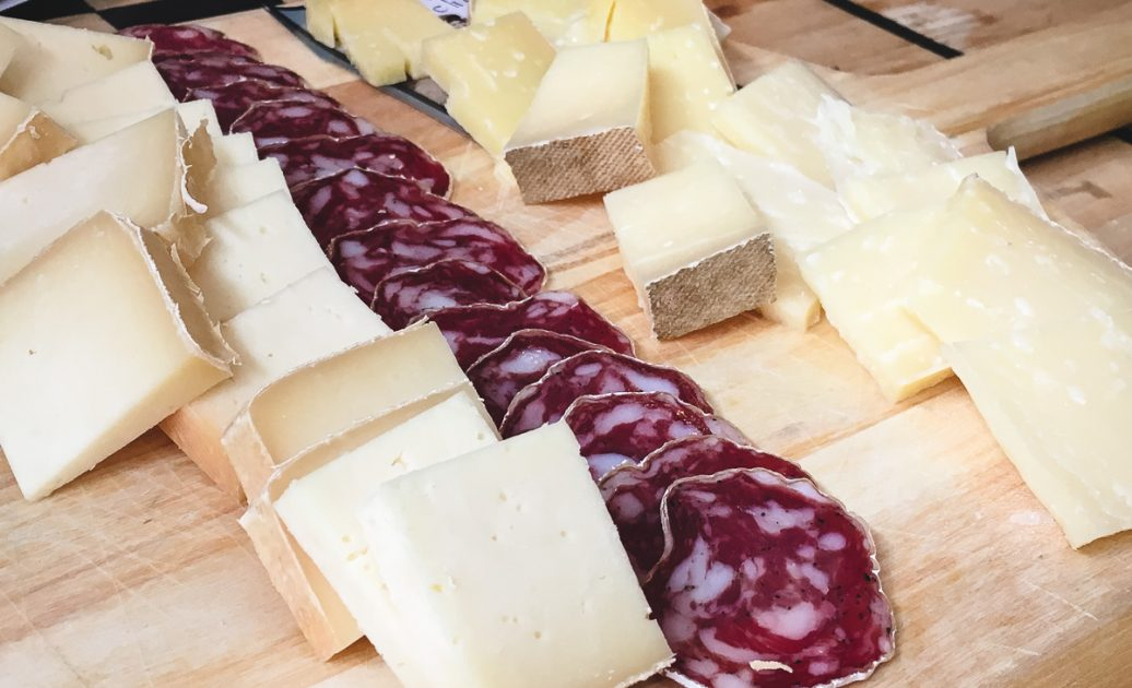 Slices of white cheeses and salami on a wooden board.