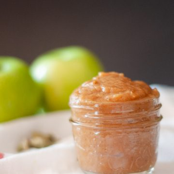 A small glass jar with apple butter. In the background are two green apples.