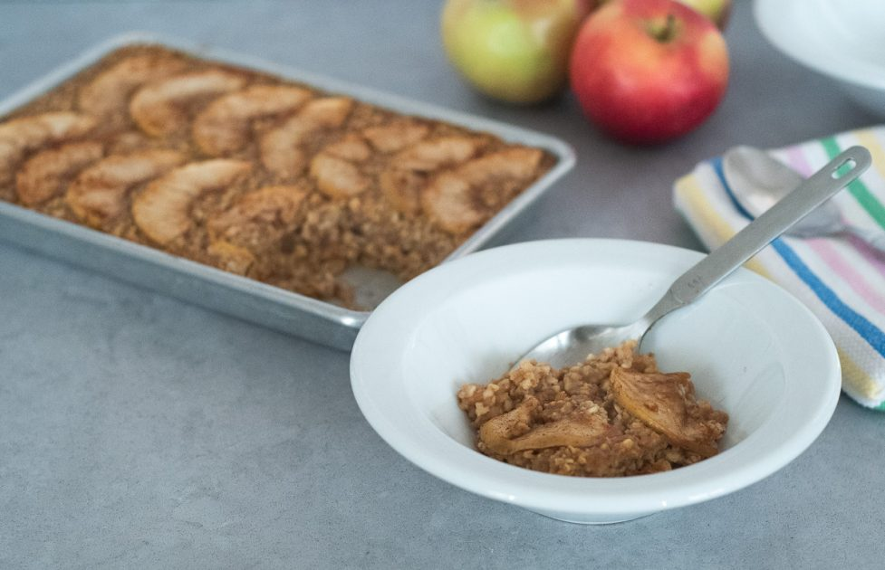 A white bowl of apple cinnamon baked oatmeal with a small sheet pan of oatmeal in the background