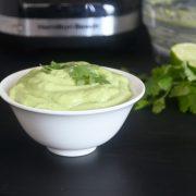 A small white bowl with light green avocado cilantro cream.