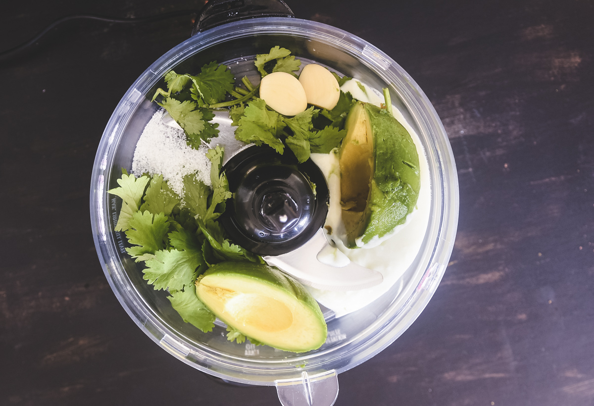 An overhead shot of a food processor bowl with cilantro, avocado, coconut milk, garlic and salt.