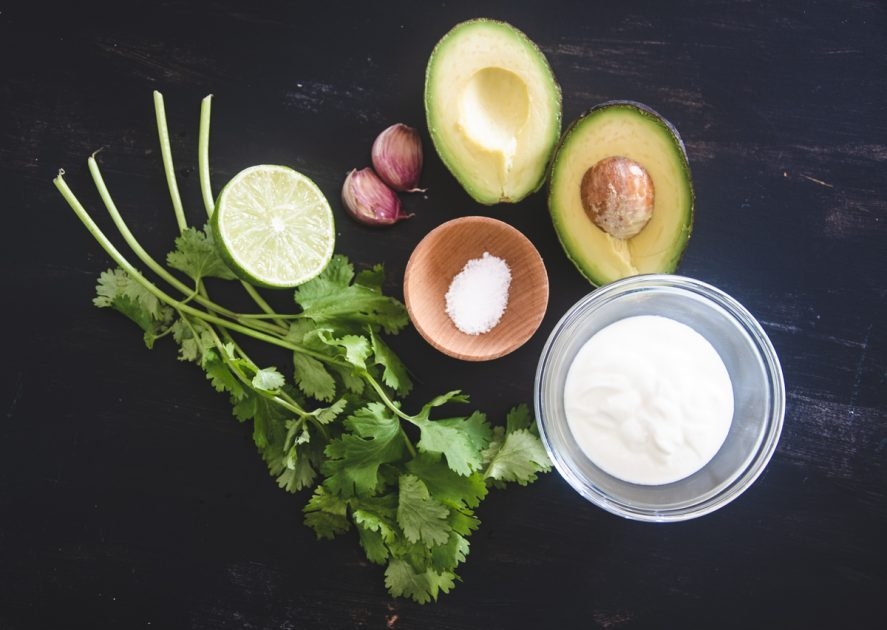 Ingredients for Avocado Cilantro Cream: A small bunch of fresh cilantro, half a lime, 2 garlic cloves, salt and coconut milk on a black table top.