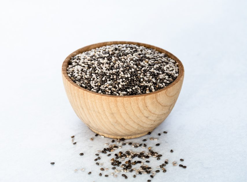 Small wooden bowl of chia seeds with a few chai seeds spilling out onto the table.