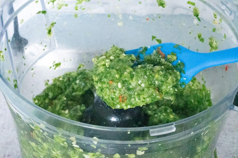 Scooping some green seasoning out of a food processor.