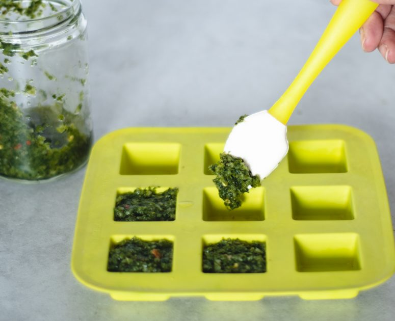 Putting freshly made green seasoning into a yellow silicone ice cube tray.