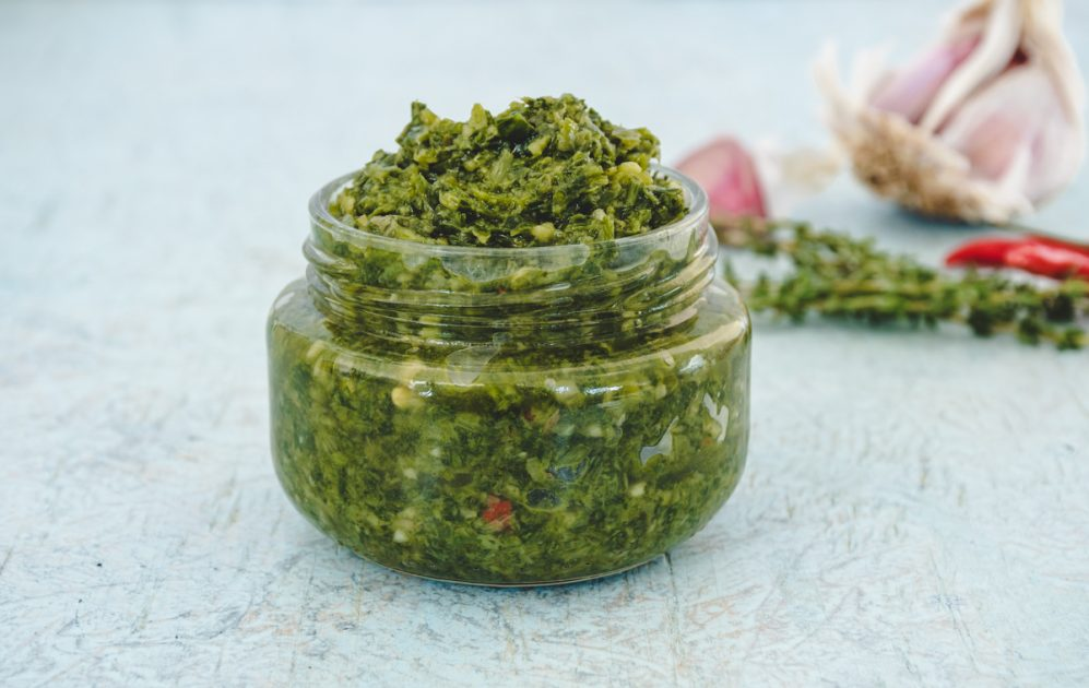 A small glass jar of green seasoning